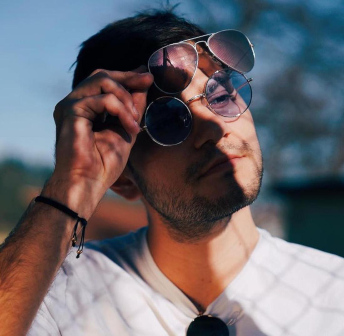 Julian Reim schaut zur Seite und hat zwei Sonnenbrillen übereinander aufgesetzt.