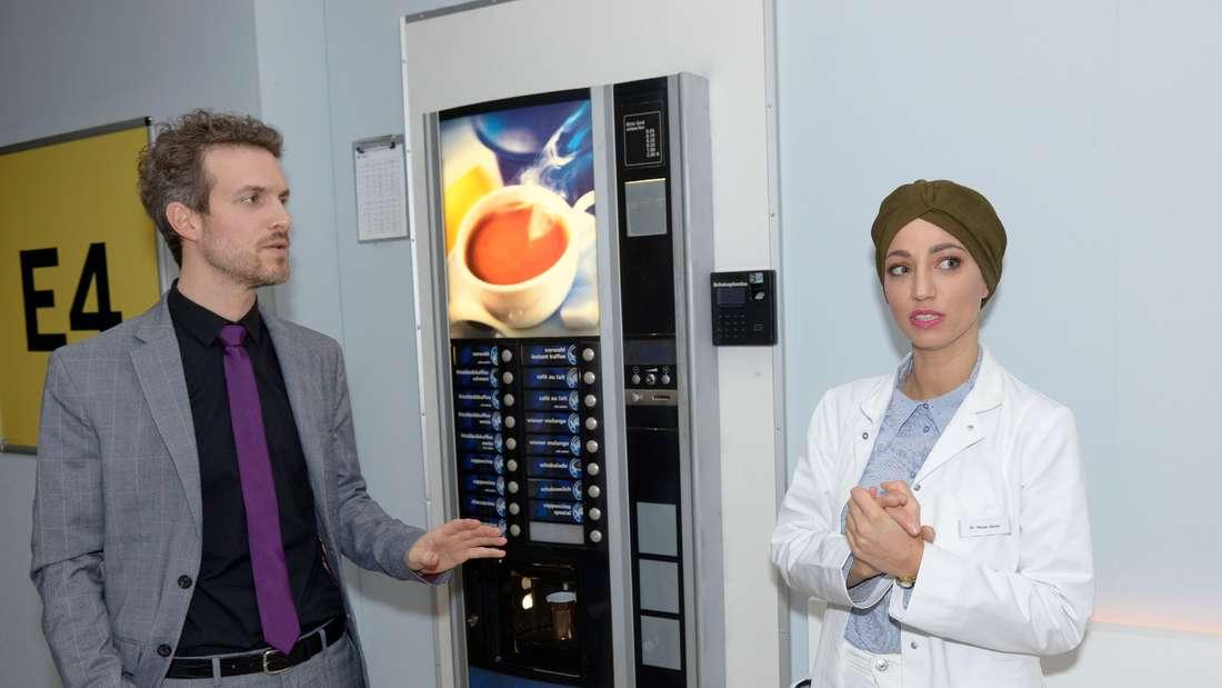 Nazan und Felix stehen im Krankenhaus vor einem Kaffeeautomaten