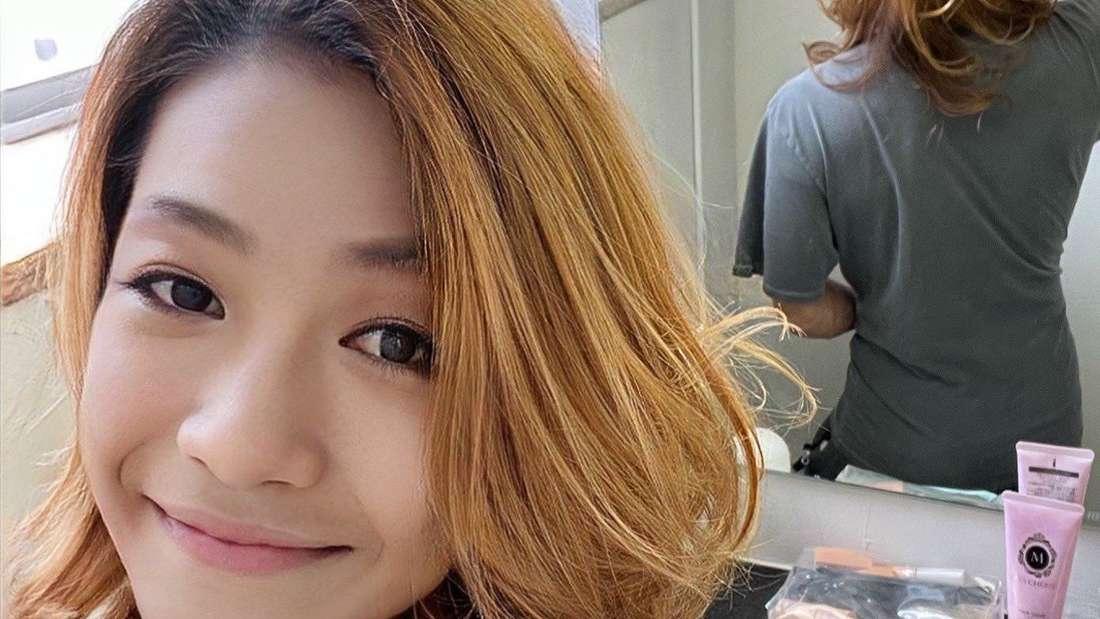 Azusaga Kuyuki steht vor einem Spiegel und macht ein Selfie.