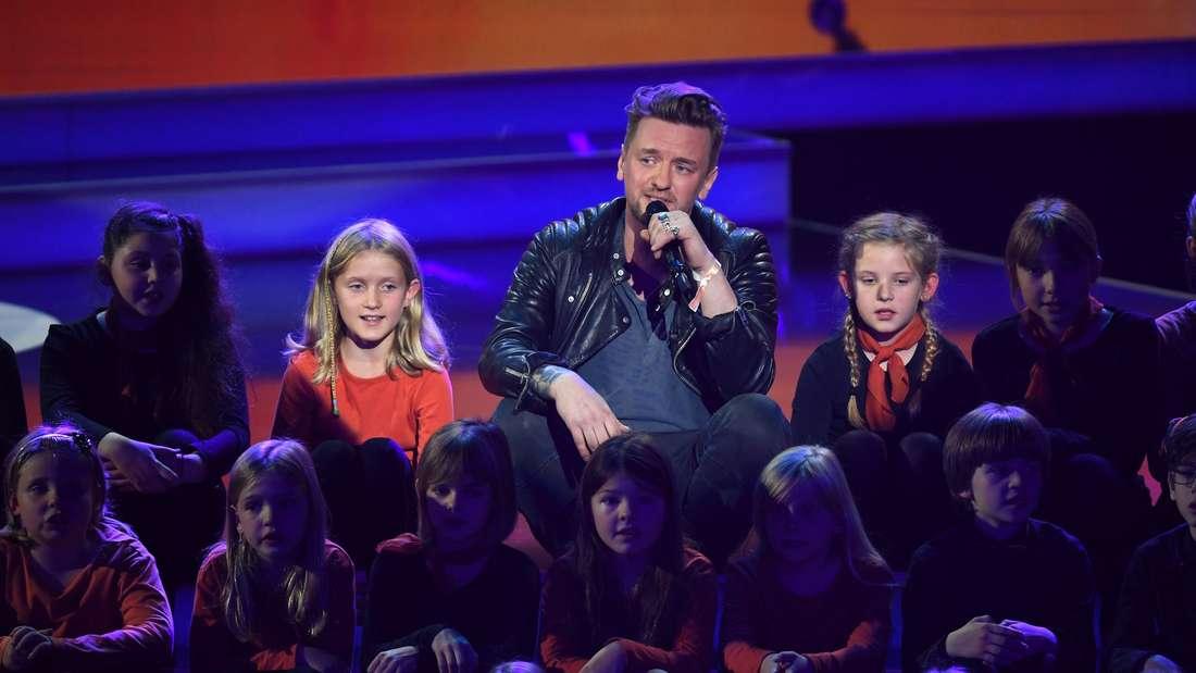 Ben Zucker sitzt zwischen Kindern auf einer TV-Bühne und singt