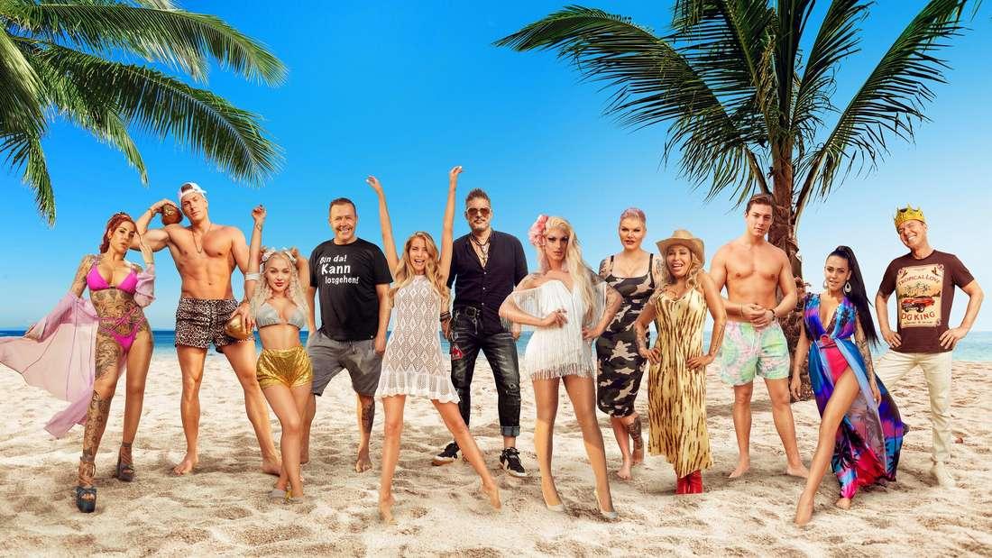 """Die diesjährigen """"Promis unter Palmen""""-Kandidaten posieren am Strand."""