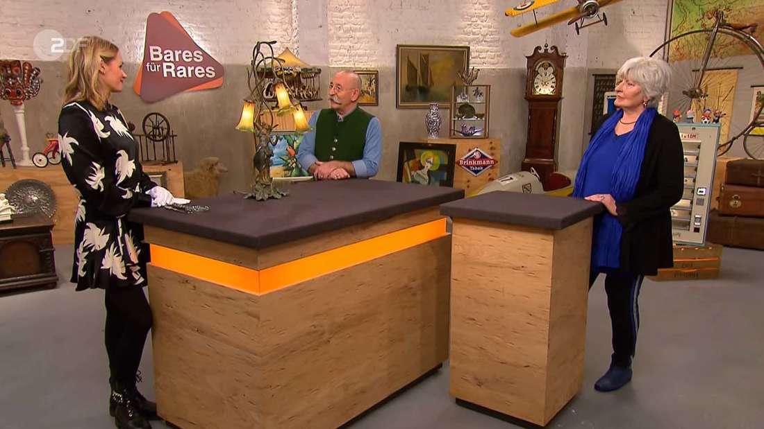 """""""Bares für Rares"""" -Expertin Bianca Berding erklärt Horst Lichter und Verkäuferin Gabriele Bottenberg um was für ein Stück es sich bei der mitgebrachten Lampe handelt"""