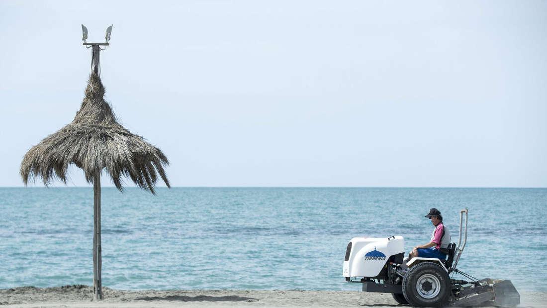 Ein Mann auf einem Fahrzeug bereitet einen Strand auf die Wiederöffnung im Sommer vor.
