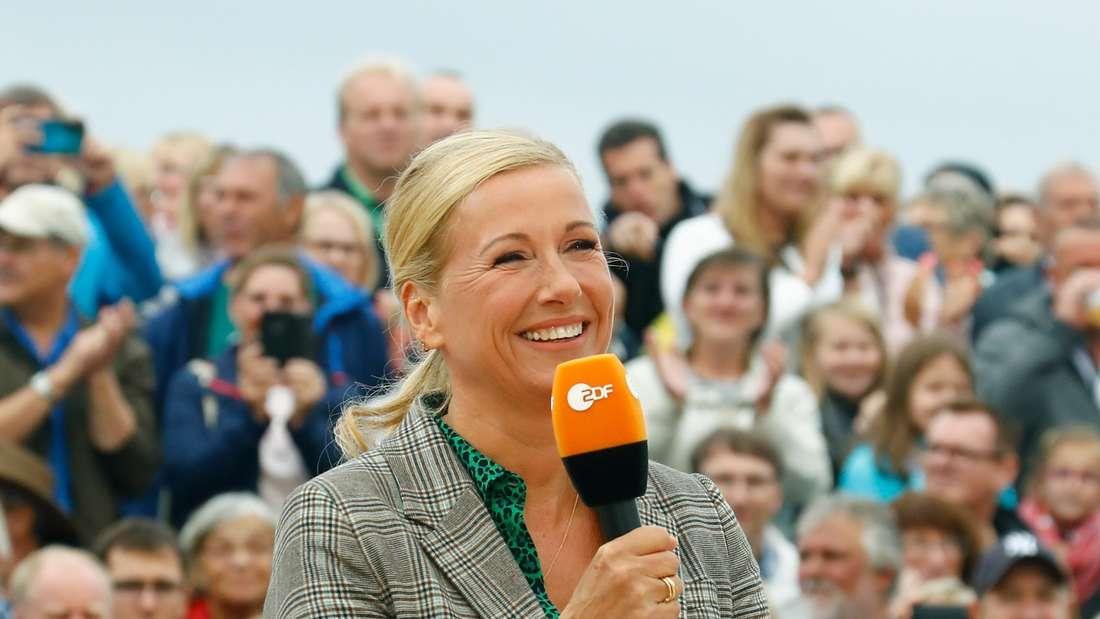 ZDF-Moderatorin Andrea Kiewel im Fernsehgarten mit Mikrofon in der Hand