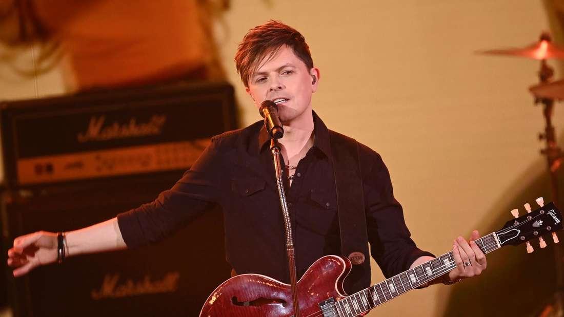 Paddy Kelly singt mit Gitarre bei einer Veranstaltung