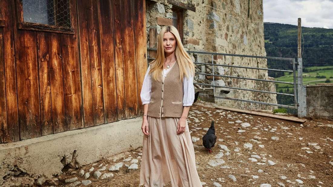 Mirja du Mont steht im Hühnergehege vor einer Bauernhütte