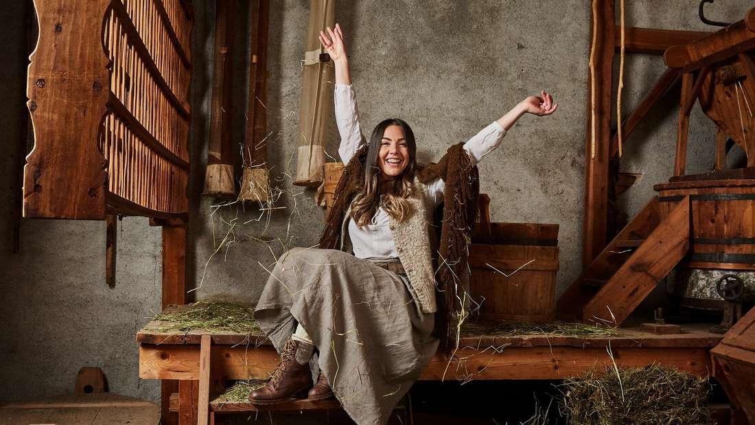 Katharina Eisenblut sitzt auf einer mit Heu bedeckten Bank
