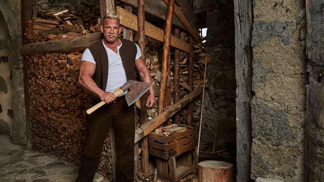 Hollywood-Matze hackt Holz mit einer Axt