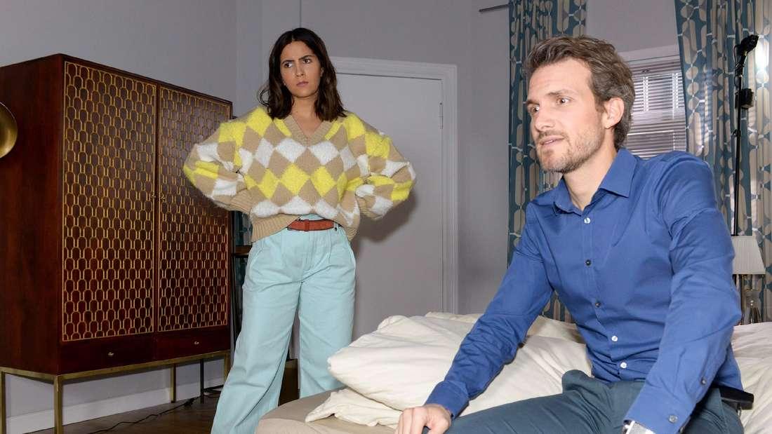 Felix sitzt auf dem Bett, Laura steht hinter ihm und hat die Hände in die Hüfte gestützt