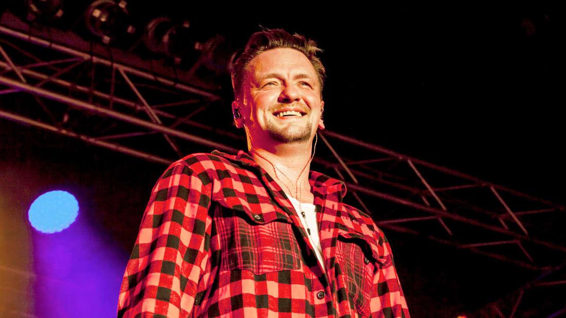 Ben Zucker lächelt und steht auf der Bühne bei einem seiner Konzerte