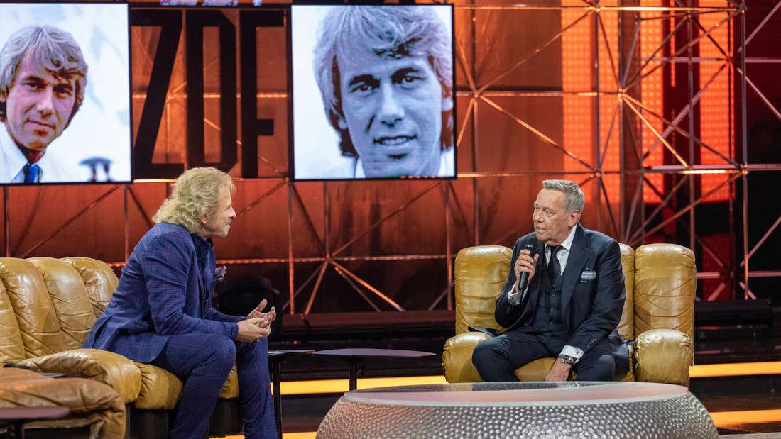 """""""50 Jahre ZDF-Hitparade - Die Zugabe"""": Thomas Gottschalk und Roland Kaiser sitzen auf Sesseln und unterhalten sich. Im Hintergrund sind alte Fotoaufnahmen von Roland Kaiser zu sehen."""