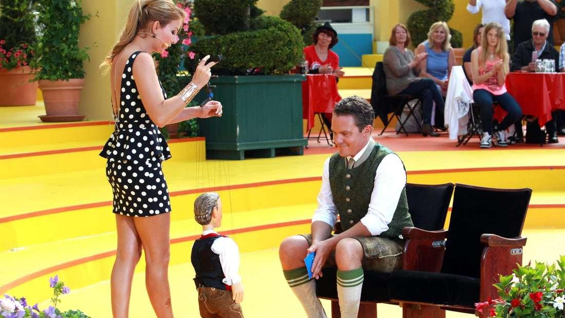 Anna-Carina Woitschack und ihre Puppe stehen vor dem sitzenden Stefan Mross in seiner Sendung. Der Moderator schaut dem Theaterspiel interessiert zu.