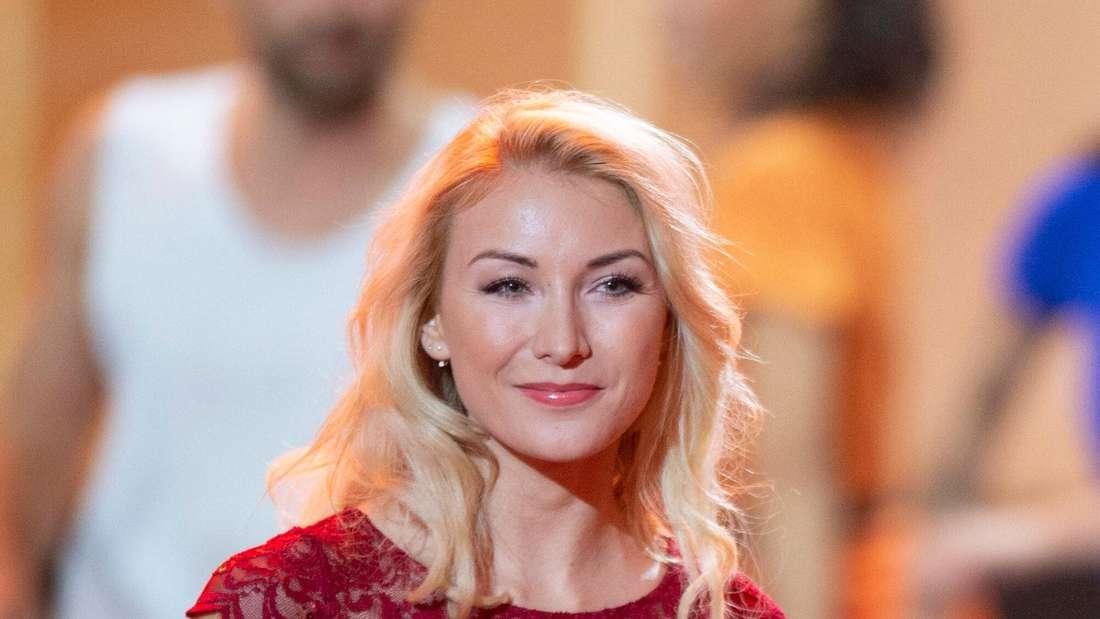 Anna-Carina Woitschack lächelt auf einer TV-Bühne und trägt ein rotes Kleid.