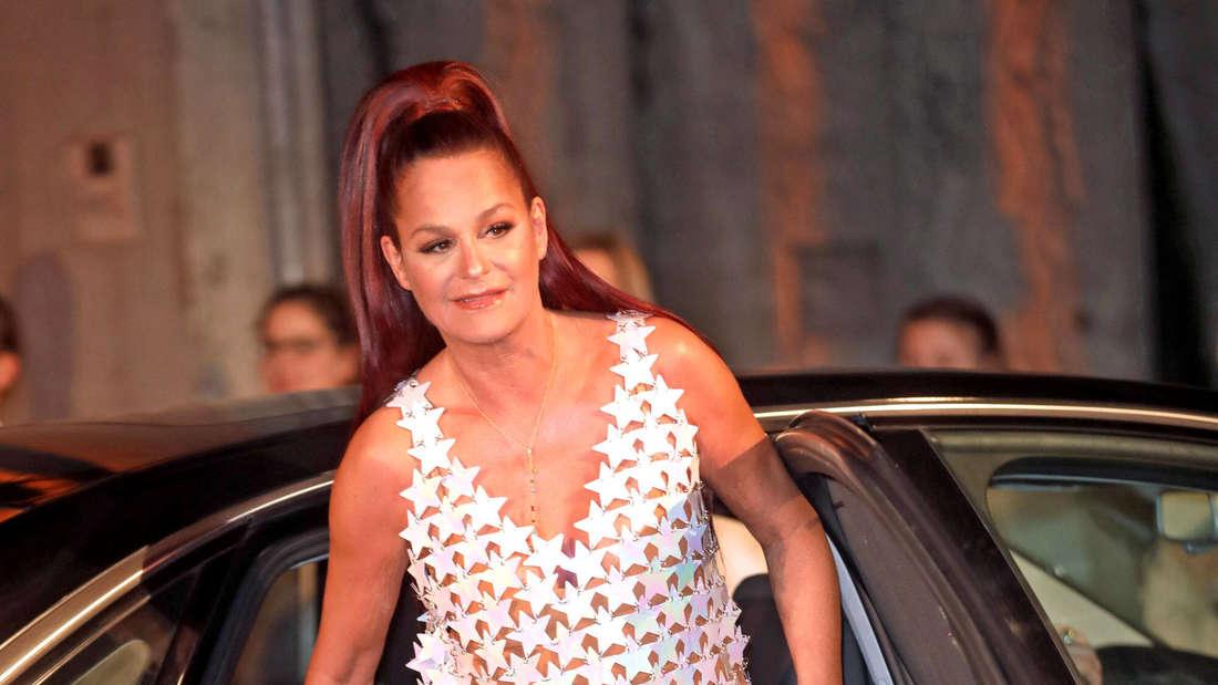 Andrea Berg steigt in einem weißen Kleid und Stiefeln aus einem Auto aus