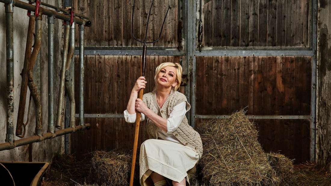 Vivian Schmitt sitzt in einer Scheune auf Heuballen
