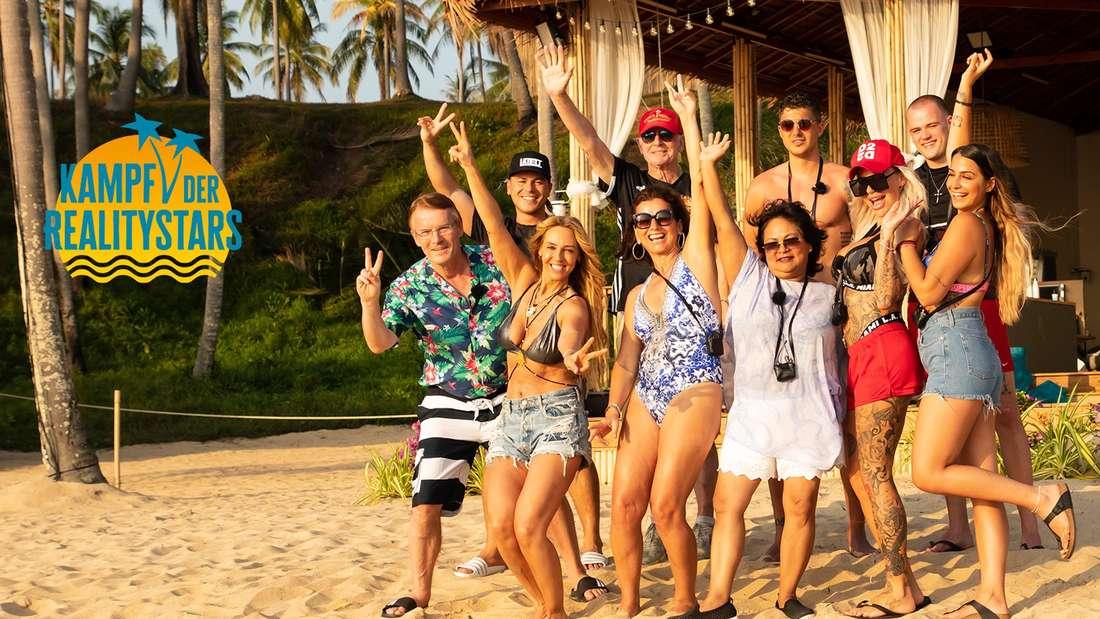 """Zehn der 25 Kandidaten von """"Kampf der Realitystars"""" haben sich am Strand von Phuket versammelt und jubeln in die Kamera."""
