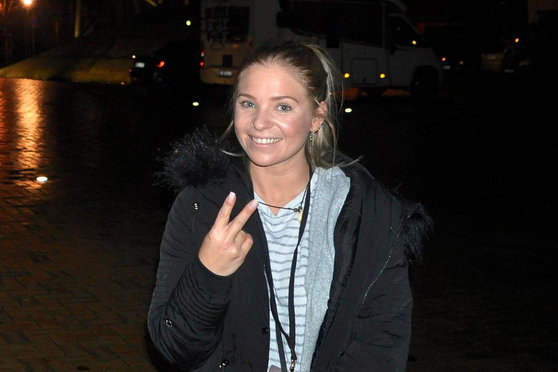Marina Marx ungeschminkt auf der Straße, lächelnd und mit Victory-Zeichen