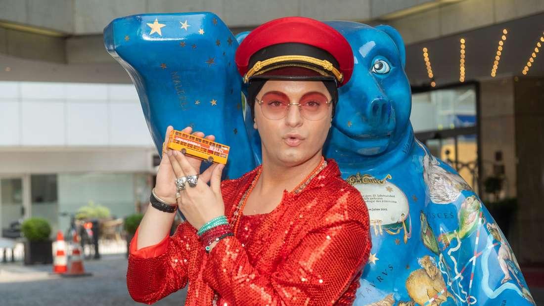 Der Entertainer und Schauspieler Julian F.M. Stoeckel steht mit einem Miniaturbus in der Hand vor einem blauen Bären
