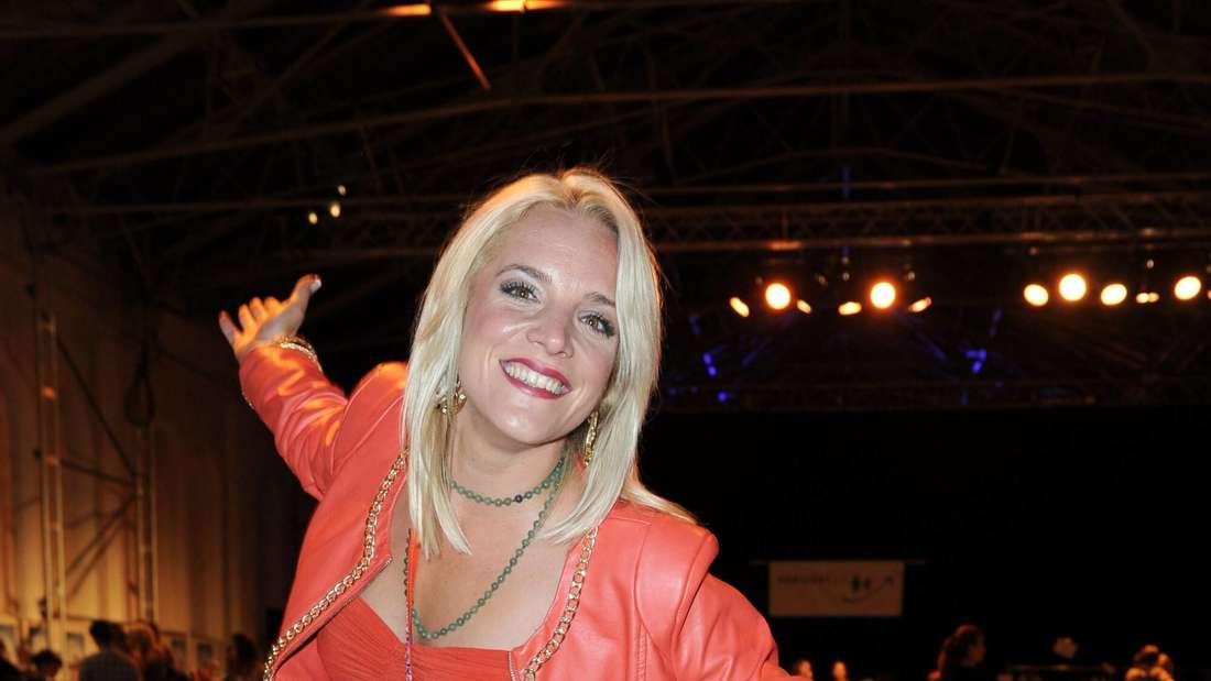 Judith Hildebrandt in einem roten Kleid, lächelt mit geöffneten Armen in die Kamera