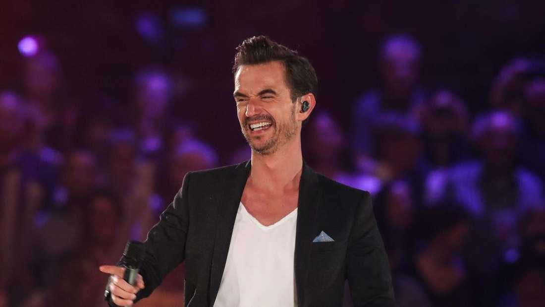 Moderator Florian Silbereisen lacht auf der Bühne einer seiner TV-Shows
