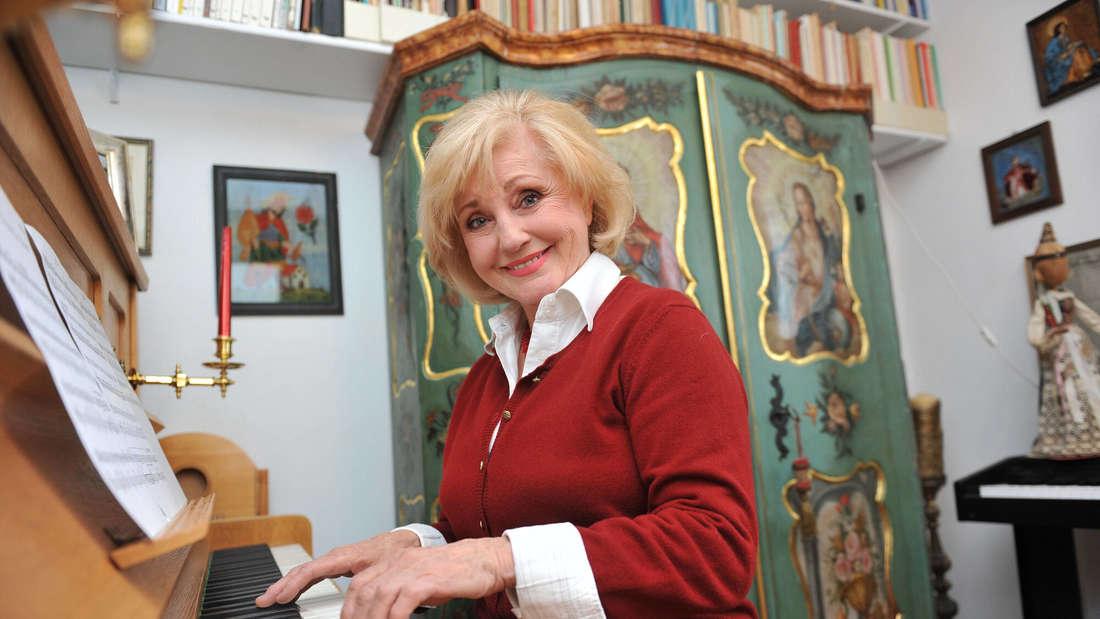 Margot Hellwig sitzt lächelnd am Klavier