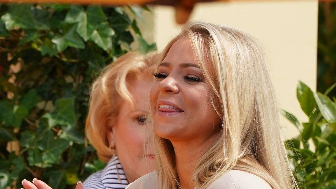 Marina Marx klatscht im ZDF-Fernsehgarten zu einem Auftritt. Dabei lächelt die Schlagersängerin und trägt einen beigen Blazer.