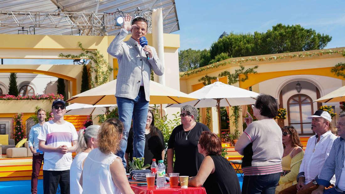 Stefan Mross steht auf dem Tisch in seiner Sendung und moderiert