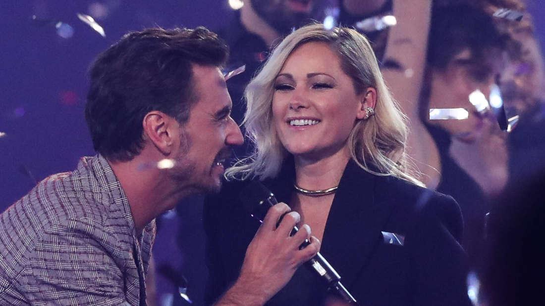 Helene Fischer und Florian Silbereisen stehen auf der TV-Bühne, umgeben von Konfetti-Regen und lächeln sich an