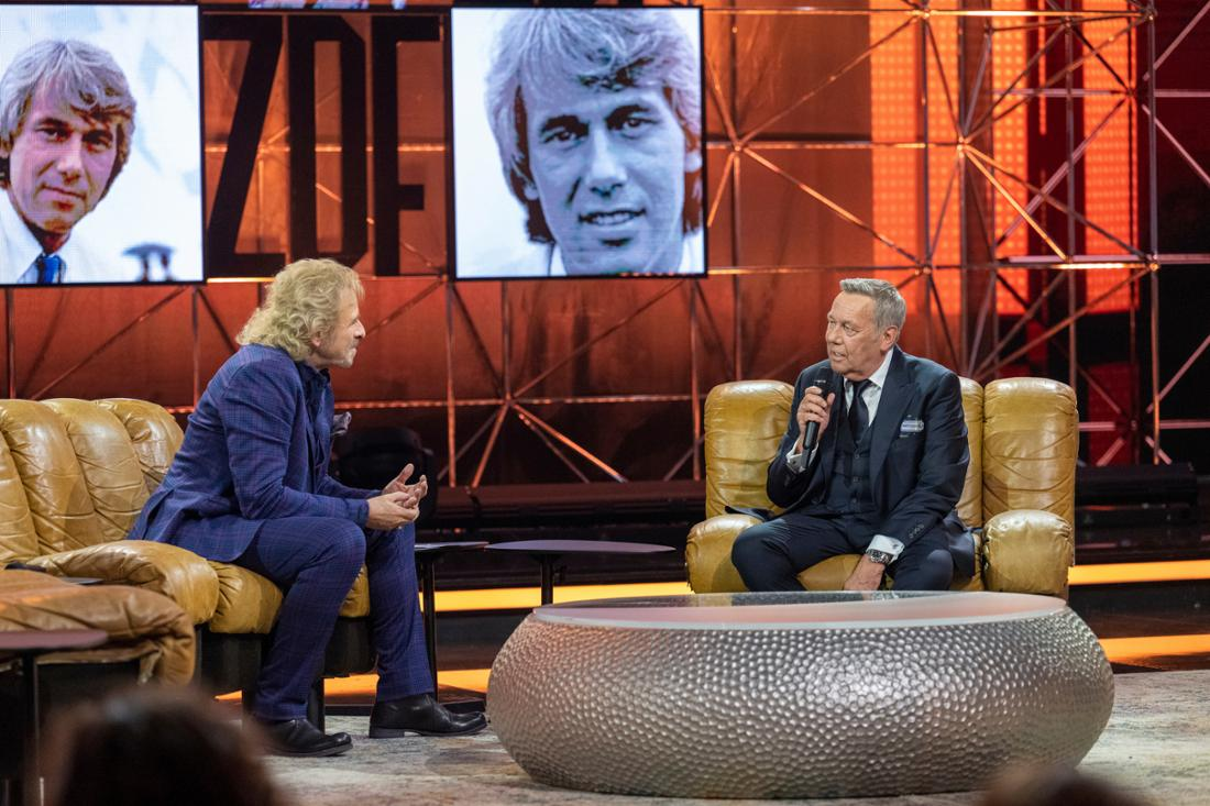 50 Jahre ZDF-Hitparade - Die Zugabe: Thomas Gottschalk und Roland Kaiser sitzen auf Sesseln und unterhalten sich. Im Hintergrund sind alte Fotoaufnahmen von Roland Kaiser zu sehen.