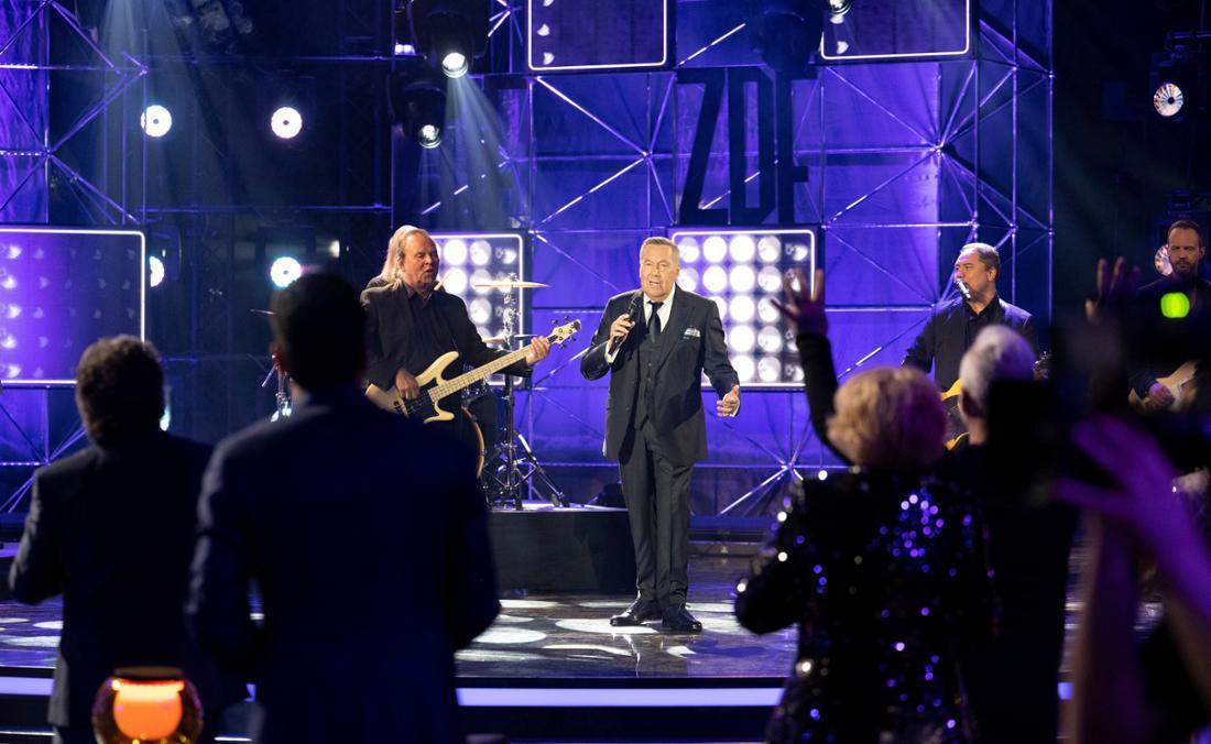 50 Jahre ZDF-Hitparade - Die Zugabe:  Roland Kaiser steht auf der Bühne und singt. Er ist umringt von seiner Band. Im Vordergrund sieht man von hinten die begeisterten Gäste der Show, die ihm zujubeln.