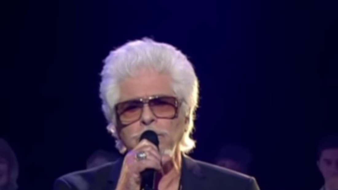 Ricky Shayne sitzt auf einem Hocker und singt seinen großen Hit der ZDF-Hitparade. Dabei ist er dunkel gekleidet, mit Brille und weißem Bart und Haaren.