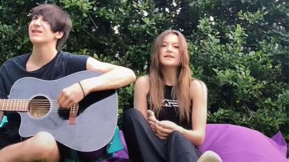 Summer und Tyler sitzen auf einer Wiese. Tyler spielt Gitarre, beide singen.