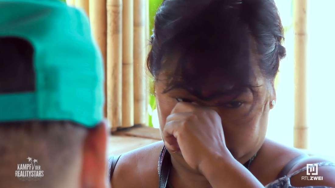 Narumol wischt sich mit ihrer Hand die Tränen weg.