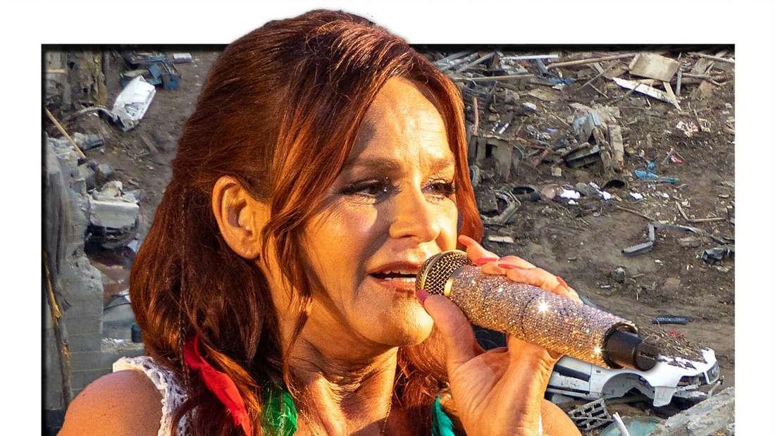 Andrea Berg singt in ein Mikro, im Hintergrund eine zerstörte Stadt (Fotomontage)