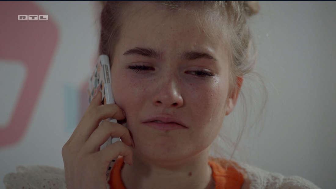 Johanna am Handy, sie hat Tränen in den Augen