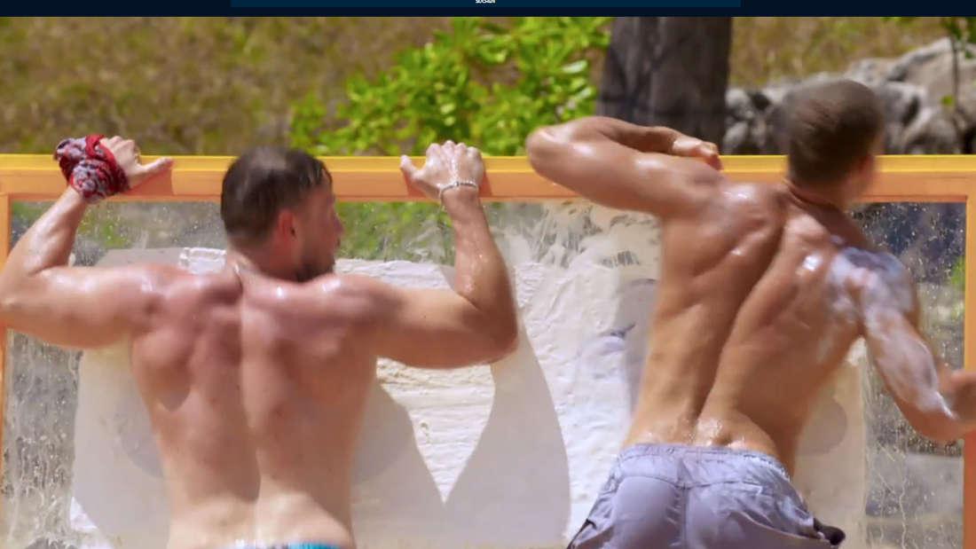 Andrej Mangold und Chris Broy rubbeln oberkörperfrei weiße Wand frei