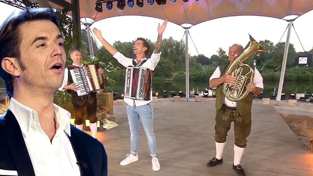 Zu sehen ist ARD-Moderator Florian Silbereisen, der ein erstauntes Gesicht macht. Im Hintergrund musiziert er mit den lustigen Almdudlern.