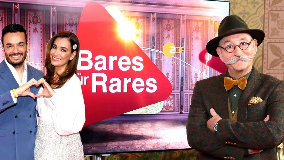 """Zu sehen ist das Ehepaar Giovanni und Jana Ina Zarrella, das mit seinen Händen ein Herz formt. Neben ihnen ist """"Bares für Rares""""-Moderator Horst Lichter platziert. Im Hintergrund ist das Logo der ZDF-Show zu sehen."""