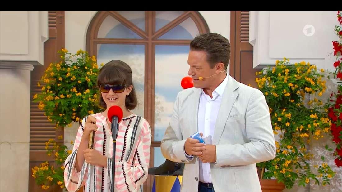 """Romy steht bei """"Immer wieder sonntags"""" vor dem roten Mikrofon auf der Bühne"""