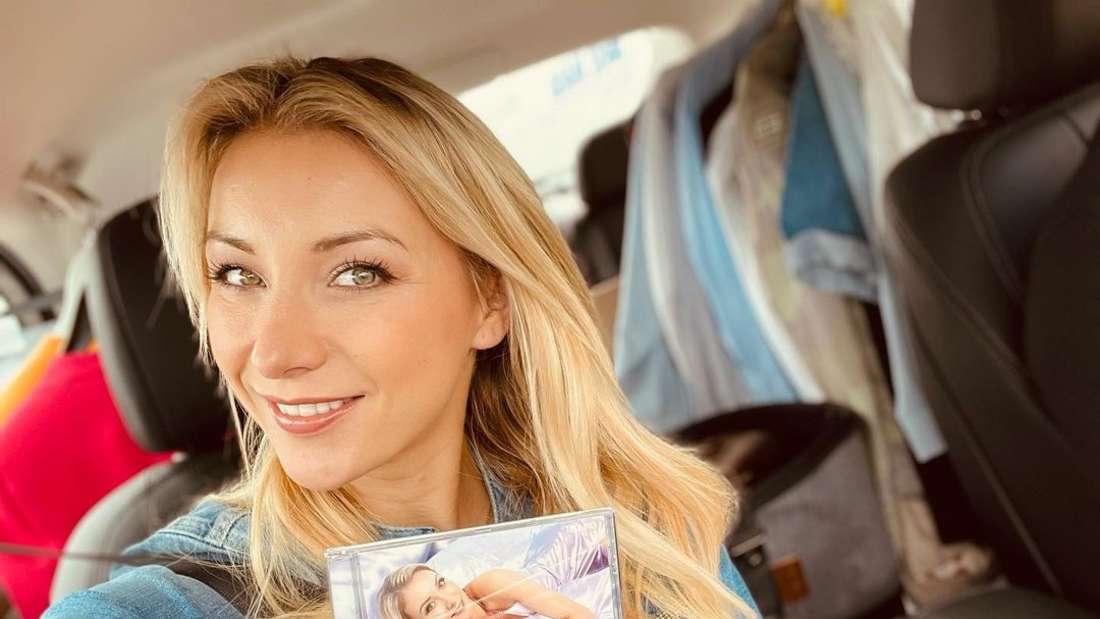 """Schlagersängerin Anna-Carina Woitschack sitzt im Auto und hält ihr fünftes Album """"Träumer"""" in der Hand."""