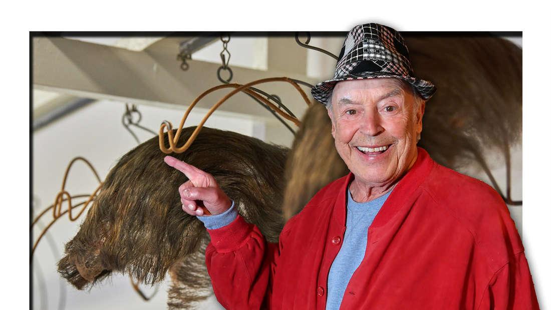 Schlagersänger Tony Marshall steht vor zwei Toupets und zeigt lächelnd auf eines davon (Fotomontage)