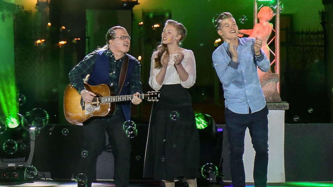 Gabriel Kelly steht mit Angelo und seiner Schwester auf der Bühne, singt und klatscht dabei