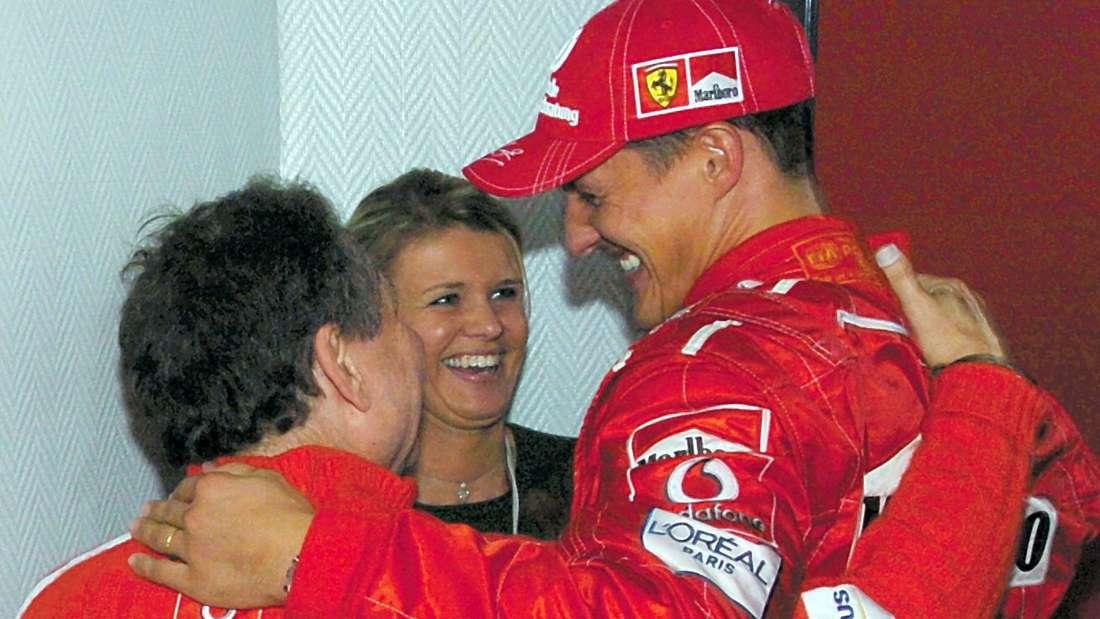 Nach dem Großen Preis von Belgien umarmt der deutsche Formel 1- Pilot Michael Schumacher (r, Ferrari) am Sonntag (29.08.2004) in Spa-Francorchamps seine Frau Corinna (M) und den Teamchef Jean Todt.