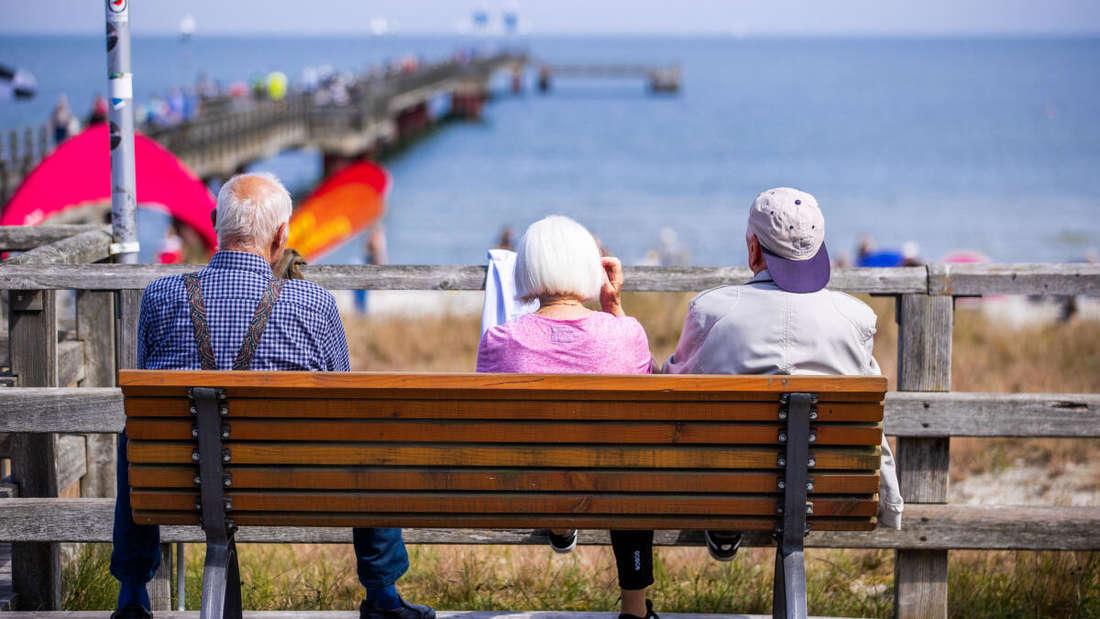 Drei ältere Urlauber sitzen auf einer Bank an der Seebrücke in Prerow.