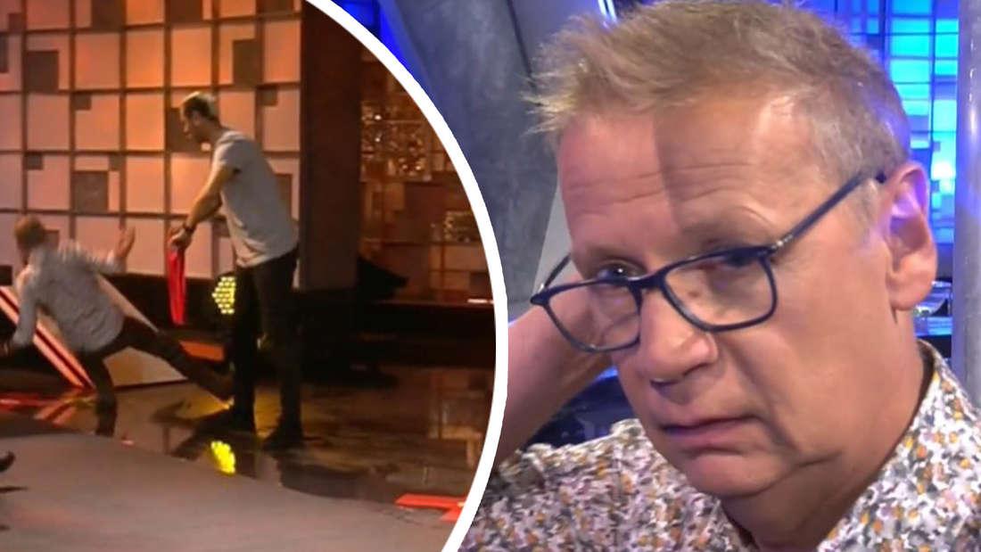 Günther Jauch stürzt und fasst sich am Kopf