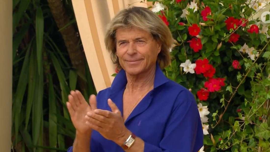 Hansi Hinterseer im blauen Hemd klatscht und schaut gelangweilt