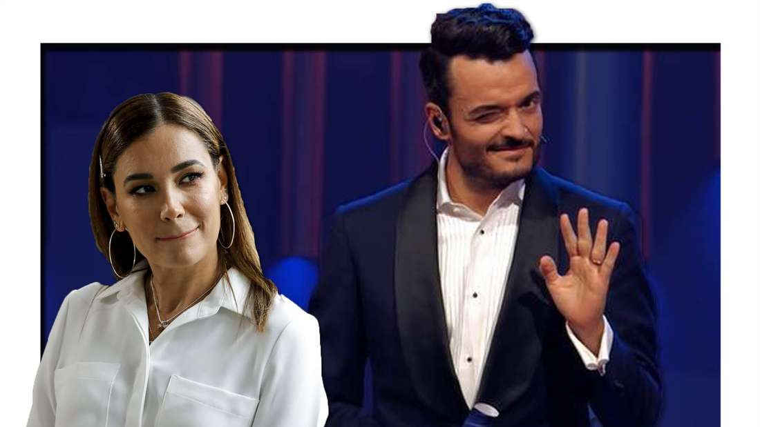 Jana Ina schaut emotionslos zur Seite, Giovanni zwinkert in die Kamera und hebt die Hand zum Winken