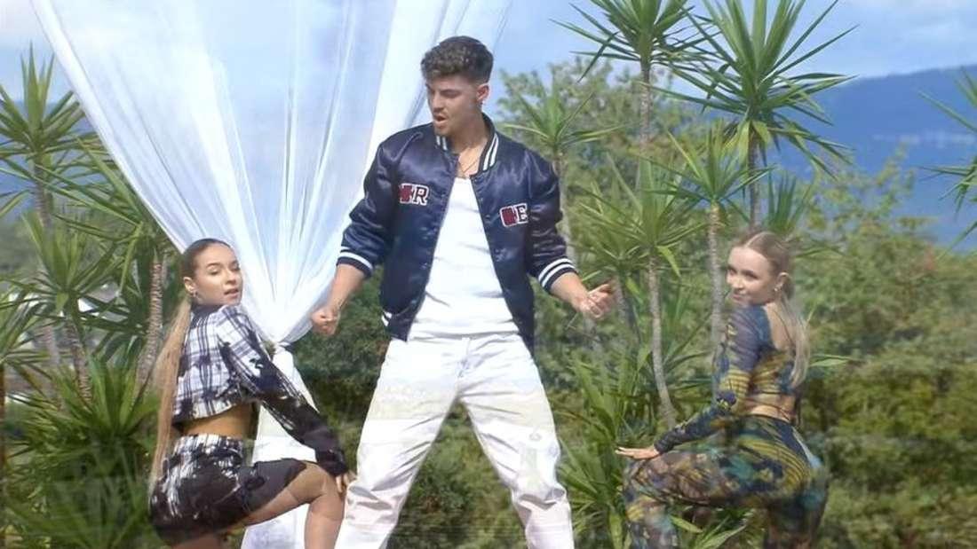 Karsten Walter in der Mitte, zwei Tänzerinnen posieren in der Hocke