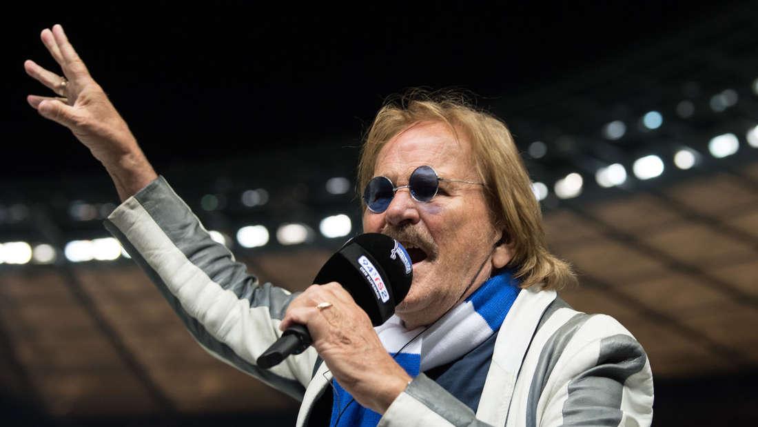 Frank Zander steht in einem Stadion und hält ein Mikro in der Hand in das der Schlager-Star singt
