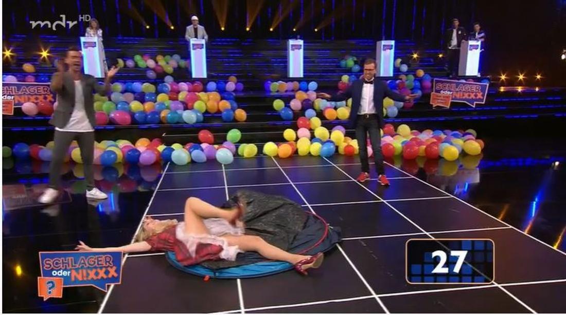 Melissa Naschenweng liegt mit ihrem Dirndl auf dem Boden